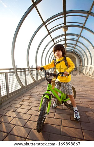 boy in yellow shirt on a bicycle in the covered bridge - stock photo