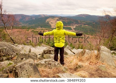 Boy in yellow warm jacket stand on a rock in a cold windy spring day. Active lifestyle, outdoor activities, hike in nature - stock photo