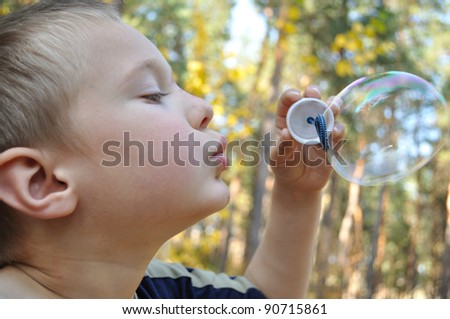 Boy inflates the bubble, the background-forest - stock photo