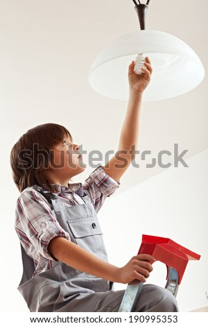 Boy installing an energy saver lightbulb - resources awareness concept - stock photo