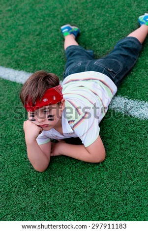 boy is bored at a football match - stock photo
