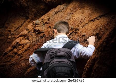 Boy is climbing the rock - stock photo