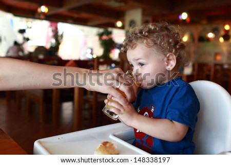 Boy is drinking orange juice in the restaurant - stock photo