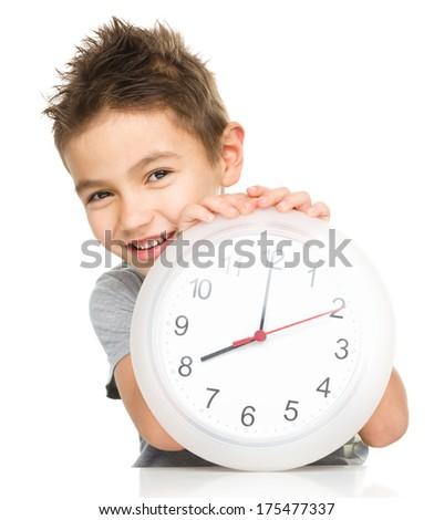 Boy is holding big clock showing eight a.m., isolated over white - stock photo