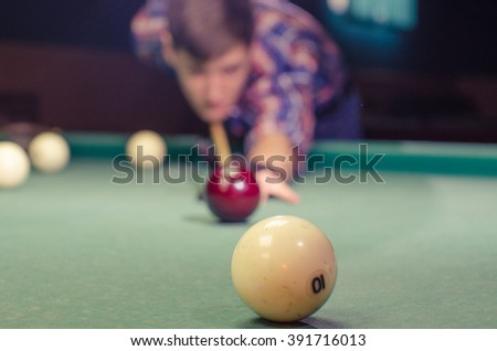 boy is not in focus aiming for shot the billiard ball which are in focus - stock photo