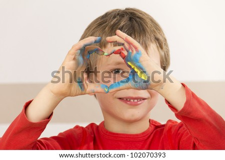 Boy is painting with finger paint and forming a heart shape with his hands - stock photo
