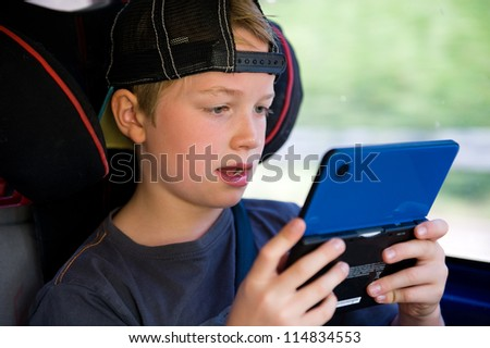 boy is playing electronic-game in the car - stock photo