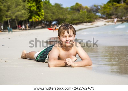 boy iy lying at the beach and enjoying the warmness of the water and looking self confident and happy - stock photo