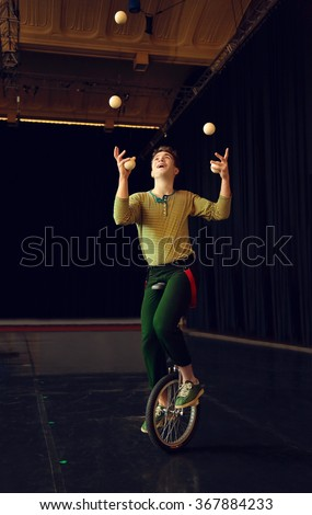 Boy juggling and riding unicycle - stock photo