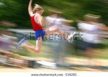 boy jumping at track meet - stock photo