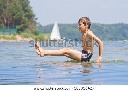 Boy jumping in ocean, playing in water, having fun - stock photo