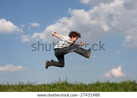 Boy jumping on green meadow - stock photo