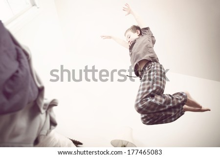 Boy jumping onto a bed - stock photo
