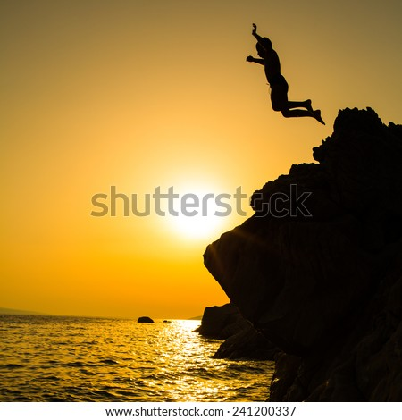 Boy jumping to the sea. Silhouette shot against the sunset sky. Boy jumping off a cliff into the ocean. Summer fun lifestyle. - stock photo