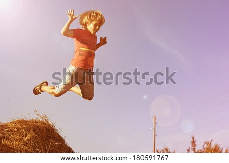 Boy jumping with haystacks. Happy child. - stock photo