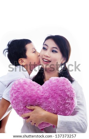 Boy kiss mother holding heart shape pillow on white background - stock photo