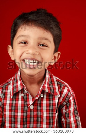 Boy laughs with his mouth in a red background - stock photo