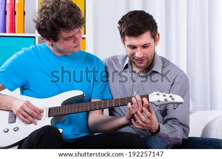 Boy learning to play on electric guitar on private lesson - stock photo