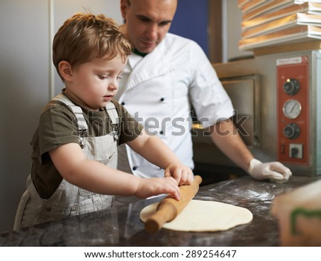 Boy learns to roll out the pizza dough - stock photo