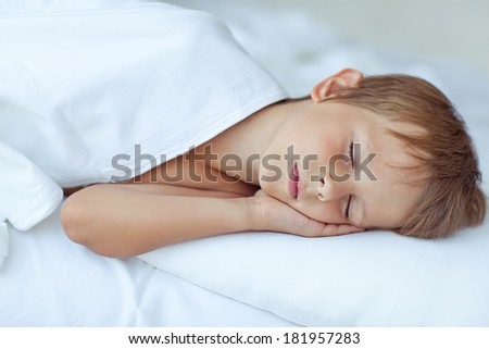 Boy, lie in bed - stock photo