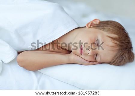 Boy, lie in bed - stock photo