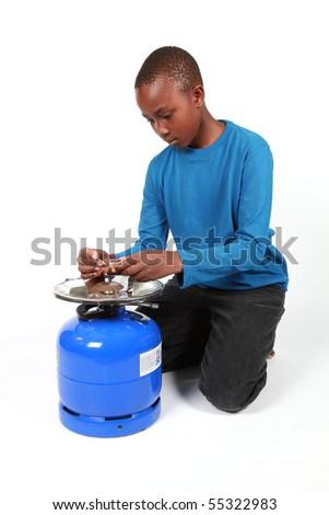 Boy lighting a fire on gas bottle - stock photo
