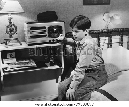 Boy listening to radio in bedroom - stock photo