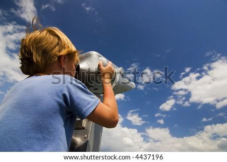 Boy look into metal binocular at beautiful sky - stock photo