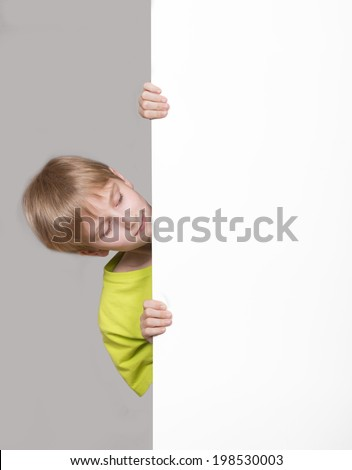 Boy looking around the corner - stock photo