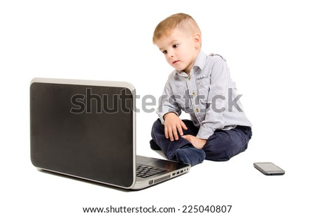 Boy looking at laptop screen sitting isolated on white background - stock photo