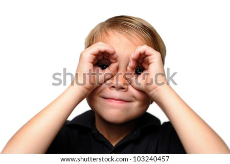 Boy Looking at Viewer Through Hands. Six-year-old boy looking through his hands as if they are binoculars. - stock photo