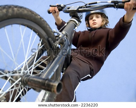 Boy looking down from BMX cycle - stock photo