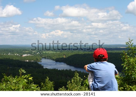 Boy looking out across a river - stock photo