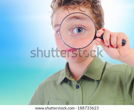 boy looking through a magnifying glass isolated on a white background - stock photo