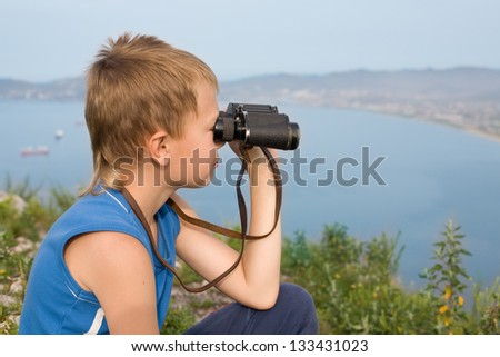 Boy looking through binoculars from the top of the mountain. In the background of the sea coast. - stock photo