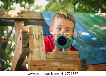 Boy looking through telescope in his fort - stock photo