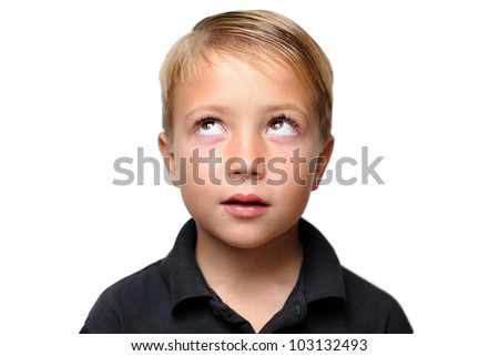 Boy Looking Upward While Thinking. Young boy facing camera with his eyes looking upward as if he is thinking. - stock photo