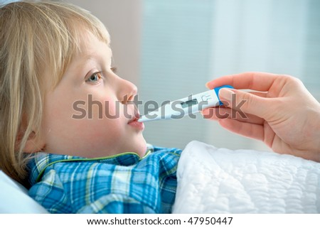 boy lying in bed with a thermometer - stock photo