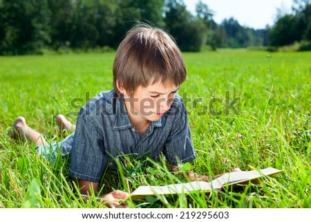 Boy lying in grass reading a book in a summer field - stock photo