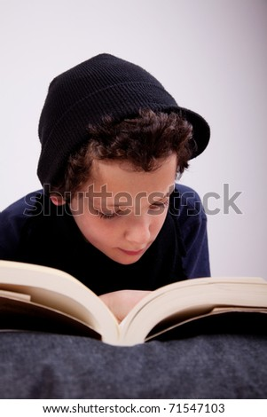 boy lying on a pillow reading - stock photo