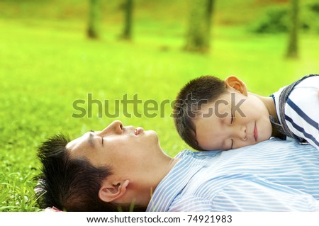 Boy lying on father. Father lying on green grass outside. - stock photo