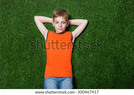 Boy lying on green grass - stock photo