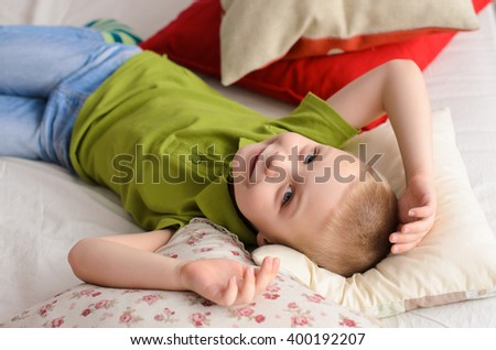 boy lying on his back in a green T-shirt. On the bed of colorful pillows - stock photo