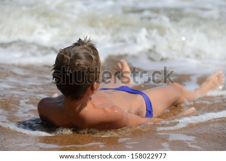 boy lying on the beach - stock photo