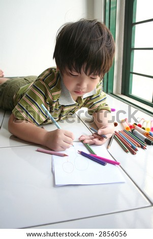 Boy lying on the floor and drawing on the paper - stock photo