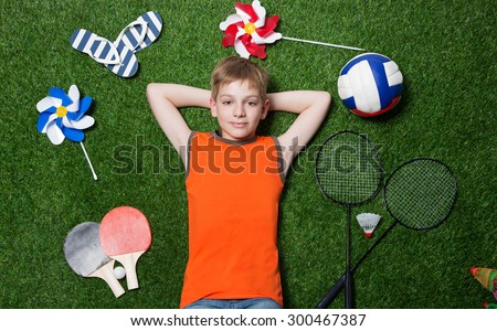 Boy lying with sport equipment on green grass - stock photo