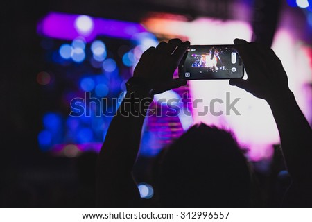 Boy makes photo with His smartphone to a concert to share the moment with friends on social networks, image with copyspace, added vintage effect, blurred effect and grain - stock photo