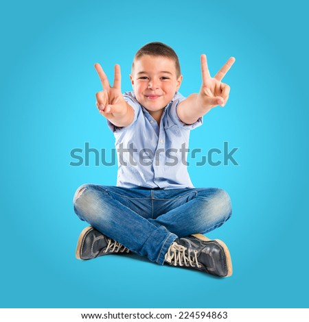 Boy making a victory sign on wooden chair over blue background  - stock photo