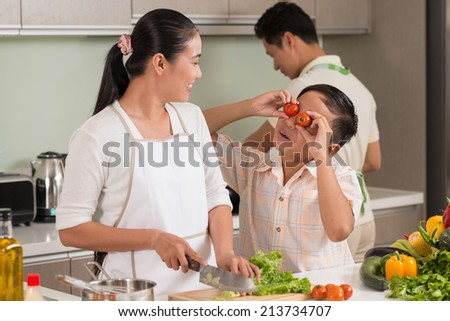 Boy making eyes from tomato to amuse his mom - stock photo