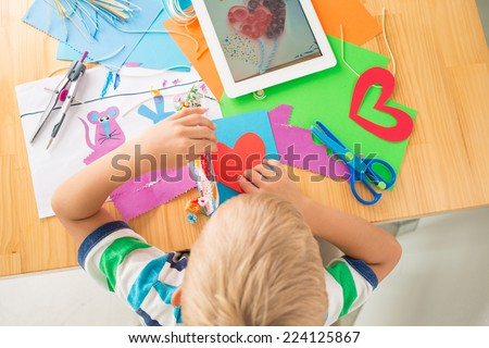Boy making greeting card according to the picture on the digital tablet, view from the top - stock photo
